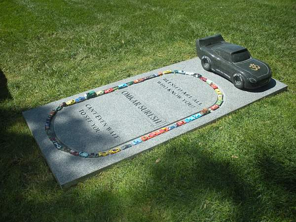 An in ground memorial with a styled car.