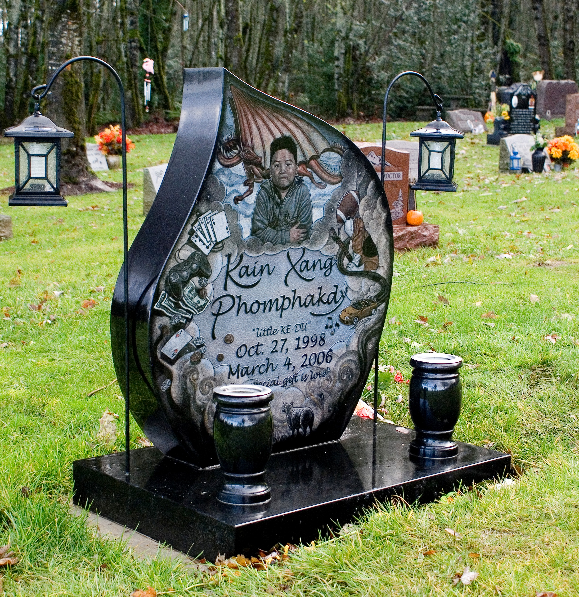 A black monument with hanging lanterns.