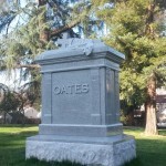 "A memorial labled ""Oates"" with a cross laying atop."